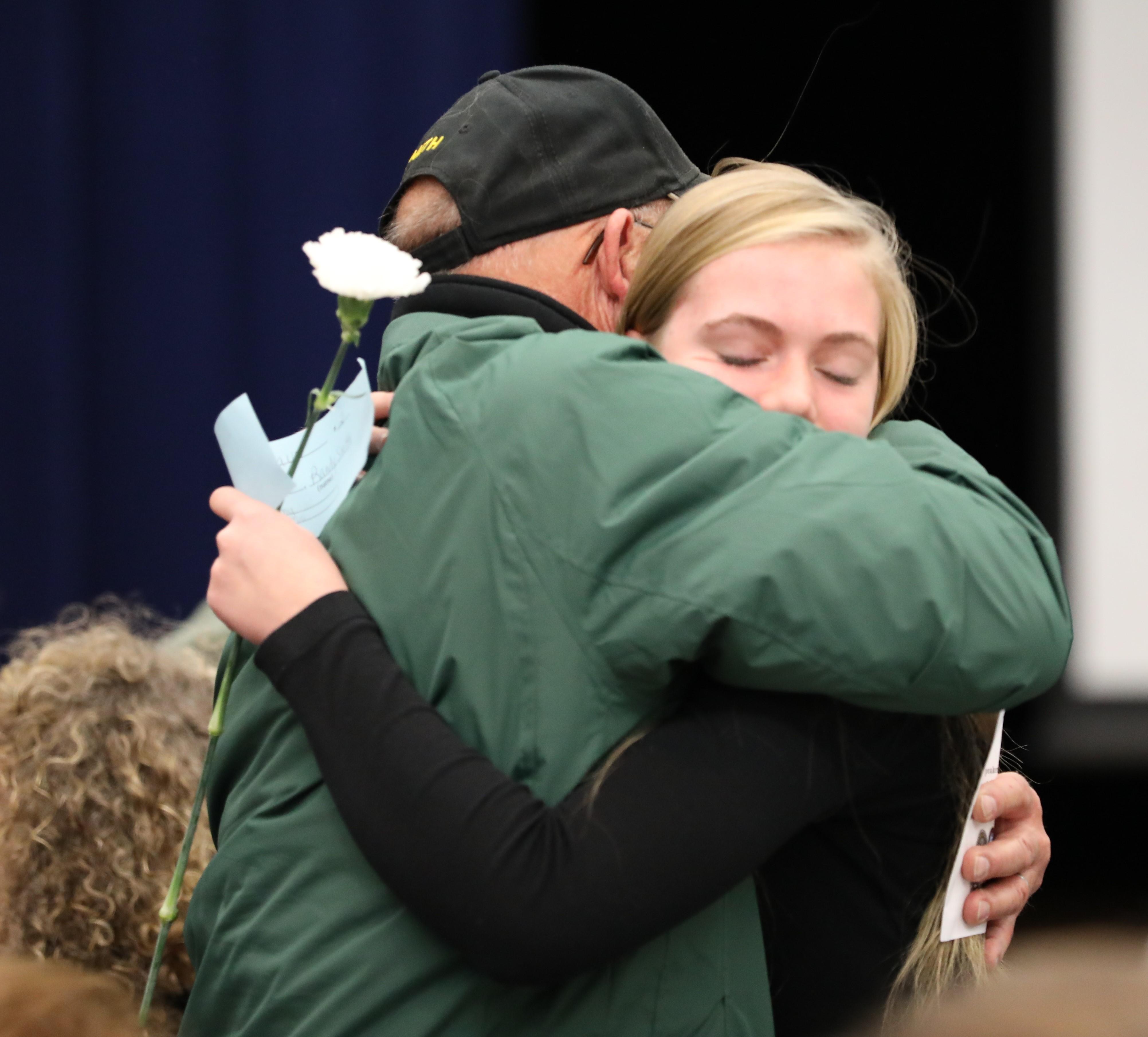 An 8th grade student hugs her Veteran family member