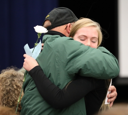 An 8th grade student hugs her Veteran family member